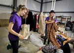 Molly Root '15, left, and Addison Mayfield '15 sort wardrobe and props as they volunteer at the Player's Theater in Utica.