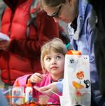 Sophie McKee, 4, gets help from her mom, Associate Professor of  Psychology Tara McKee, in making a sparkly mask.
