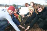 Community members, including President Joan Stewart, right, plant bulbs at the Farm Garden.