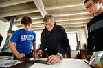 Master Printer Ted Shuart helps Hamilton students Enrico Gonzalez '16, left, and Max Newman '16 set a line of type.