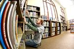 Bret Turner '13 organizes and refiles books in the Utica Public Library.