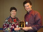 AMS president Vicki Martin presents Pat Reynolds with a plaque at the society's annual meeting.
