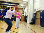 Rebecca Rees '16 coaches players in a game of basketball.