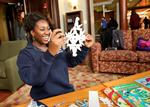 Maybelline Acquaye '14 reacts with surprise after unfolding a paper snowflake she created.