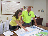 Aubrey Coon '16 reviews engineering schematics of shoreline restoration with Village of Sylvan Beach Administrator Joseph Benedict.