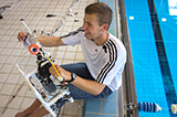 Jonah Boucher '17 works on a custom built remote operated vehicle at Bristol Pool.