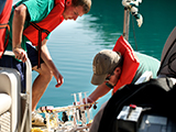 Rob Clayton, left, and Daniel Lichtenauer, remove a sample syringe containing bacteria samples from Green Lake.