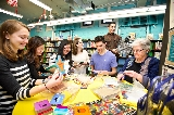 HAVOC members and Library Director Darby O'Brien look over early literacy program backpack items at the Utica Public Library. From left Abby Uehling '18, Caitlin Yu '19, Jill Fu '19, Anna McCluskey '18, Aaron Oh '18 (standing behind), James Mesiti '17, and Library Director Darby O'Brien.
