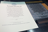 A copy of the newly printed honor code print is placed next to a type form.