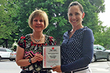 Colleen Pellman, left, accepts a plaque from Sarah Stevens of the American Heart Association.