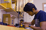 Steve Laurent Cunden '18 works on a robotic arm.