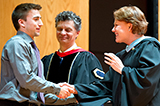 Alex Mitko '16 receives congratulations from Dean of Students Nancy Thompson and Dean of Faculty Patrick Reynolds.