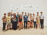 Hamilton NYC Program students in front of Glenn Ligon's neon installation Ruckenfigur.