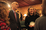 Hamilton President-elect David Wippman talks with students and alumni following the choir's performance in St. Paul, Minn. Caitlin McQuade '18 is at left and Mackenzie Leavenworth '15 is on the right.