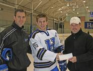 Head coach Norm Bazin (left) and team captain Joe Buicko '11 (middle) present a $1,200 check to Clinton Youth Hockey board member Todd Jury.