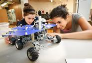 Emily Winter '14 (left) and Rose Berns-Zieve '15, admire a LEGO replica model of the Mars Rover at the Children's Museum in Utica during a visit by Outreach Adventure students.