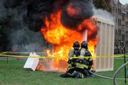 Clinton volunteer firefighters spray water on the mock dorm room fire.