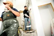 Ray Cyr, a longtime custodian at Hamilton, lets volunteer Fran Rose by as he paints in a stairwell in a house being renovated by Habitat for Humanity. Cyr joined other Hamilton employees in the renovation as part of Employee Service Day on MLK Day.