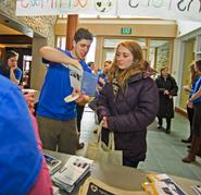 Ed Reed '13 explains the orientation schedule to Cameron Dunne '16 while new students sign-in at the Sadove Student Center.