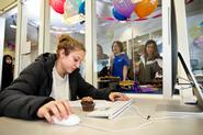 With a party going on behind her, Kayla Winters '13 works with a cupcake at hand, during a birthday celebration for the Writing Center.