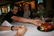 Students grab a piece of challah during Rosh Hashanah dinner.