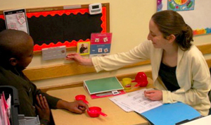 Sarah Dreyer-Oren '12 with a student at NECC.