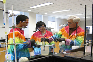 From left, Felipe Garcia '14, Joshua Ho '15 and Professor of Chemistry Tim Elgren work in a lab.