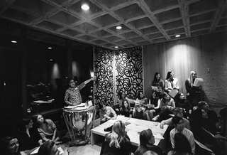 Assistant Dean and Associate Professor of English Louise Slipper hands out course assignments to the first Kirkland College class in September 1968 during an orientation session in the lounge of McIntosh Hall. A kettledrum temporarily stored in the lounge<br />Photo: The New York Times