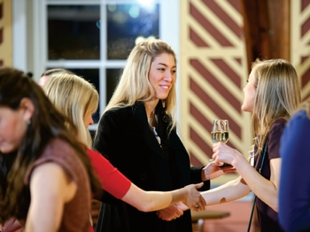 Seniors Elizabeth Ruemelin (center), Alex Rued (right) and Katie Kearney practice their social skills during a senior networking reception at the Events Barn. The event helps seniors hone their ability to interact in informal professional settings.