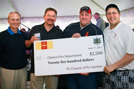 Jack Withiam '71, Pat Murphy '80, Clinton Fire Department Chief Mark Young and Pat Gilrane '83 pose with a check for the Clinton Fire Department at the Psi Upsilon house party.