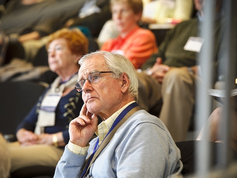"John Reilly '63 listens to the panel during the Alumni College, ""Health Care Coverage Affordability."""