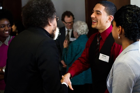 Wilne Arias '15 speaks with Dr. Cornel West at the reception.
