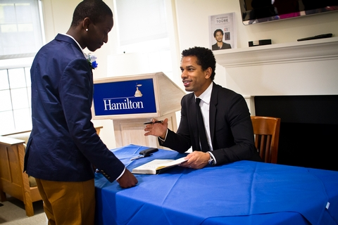 Touré speaks with students and signs books.