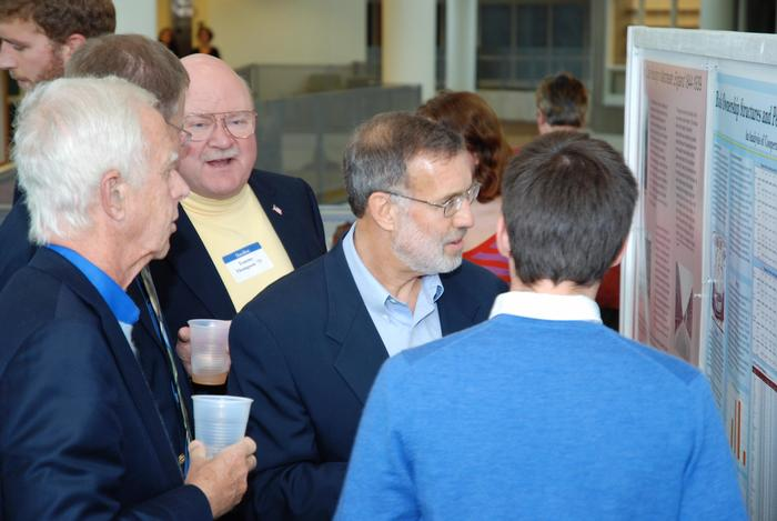 Alumni and faculty members chatted with a student presenter during the summer research poster session
