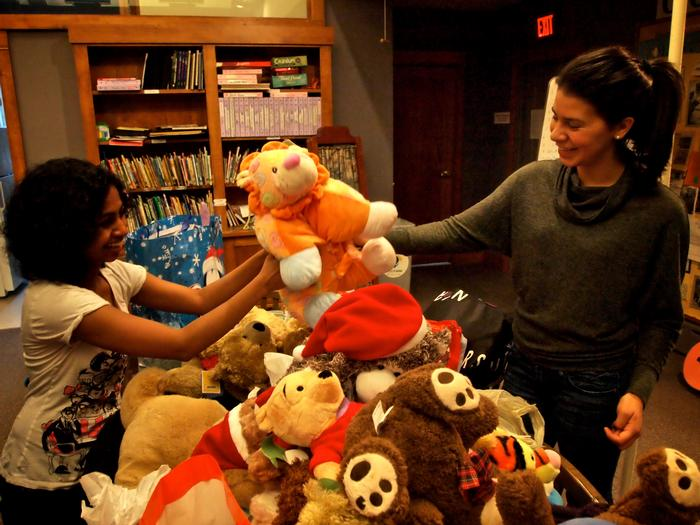 COOP Senior Fellow Ramya Ramnath '13, left, helps Elizabeth Rodriguez '15, Mitten Tree coordinator, with some of the toys collected.