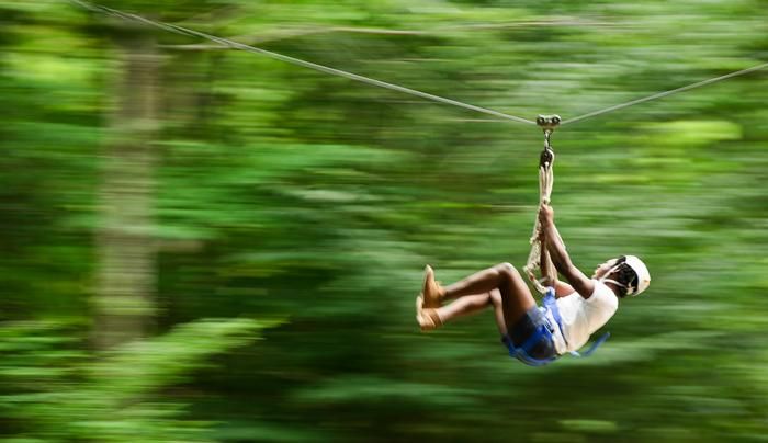 Sean Smith '15 laughs while ziplining during Adirondack Adventure. PHOTO: BY NANCY FORD