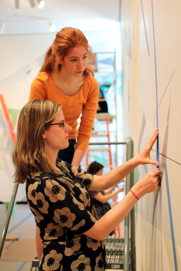 Artist Danielle Tegeder, kneeling, works on the wall with Candice McCardle '15. PHOTO: BY VICTORIA LIN '15