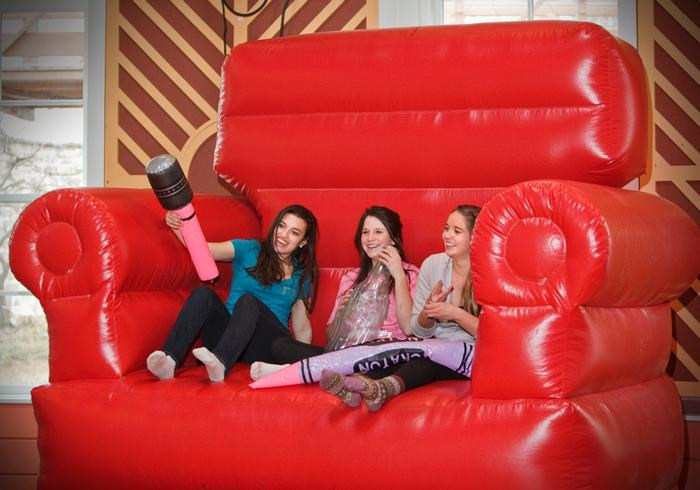 Students pose for a picture in a giant inflatable chair at the FebFest carnival. PHOTO: BY LAURA LAUREY