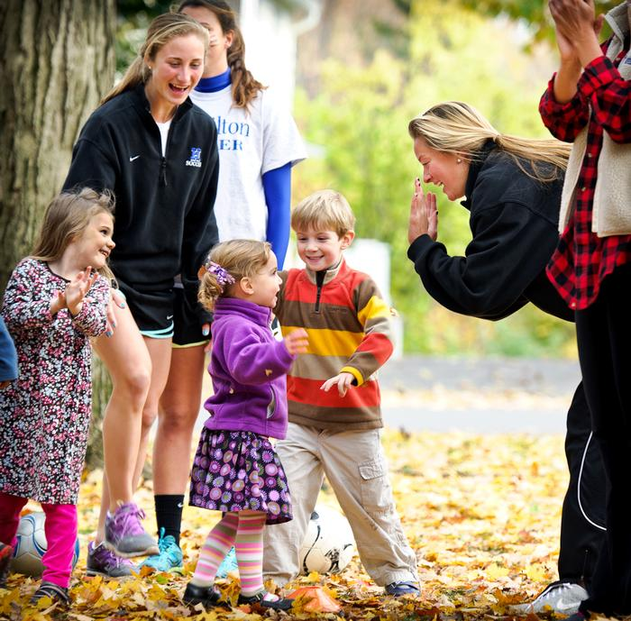 Members of Hamilton's Women's Soccer team and Victoria Freeman '16, right, cheer on three-year-old Clara Shaw as they play relay games at Fall Fest. PHOTO: BY NANCY FORD