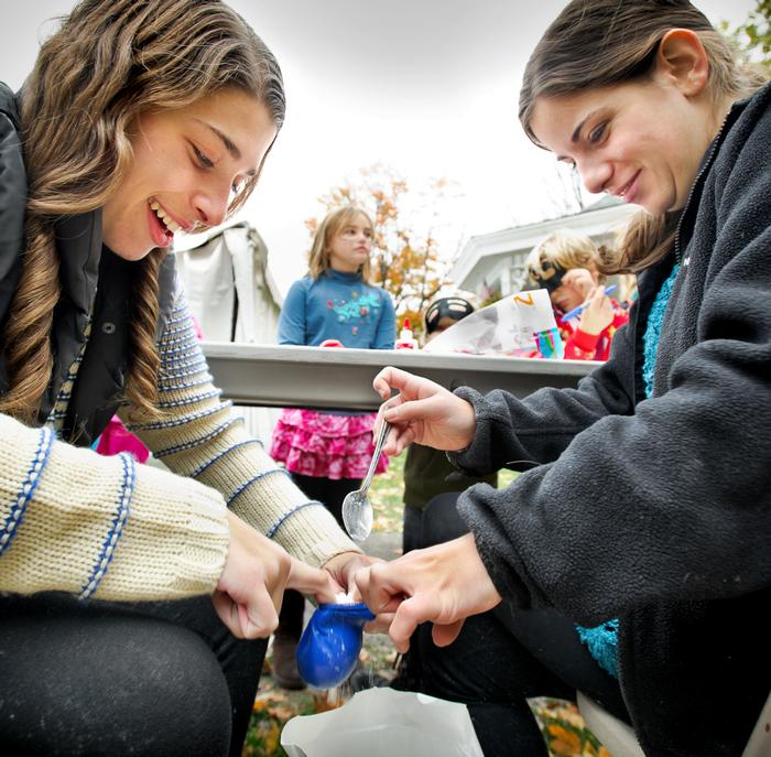 Talia Levine '15 and Emily Malter '15 stuff flour into a balloon to make stress balls for children to decorate.  PHOTO: BY NANCY FORD