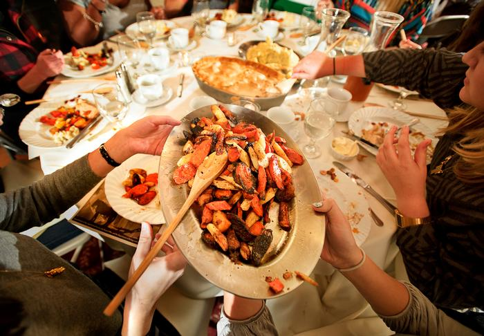 A dish of Roasted Root Vegetables is passed.  PHOTO: BY NANCY FORD
