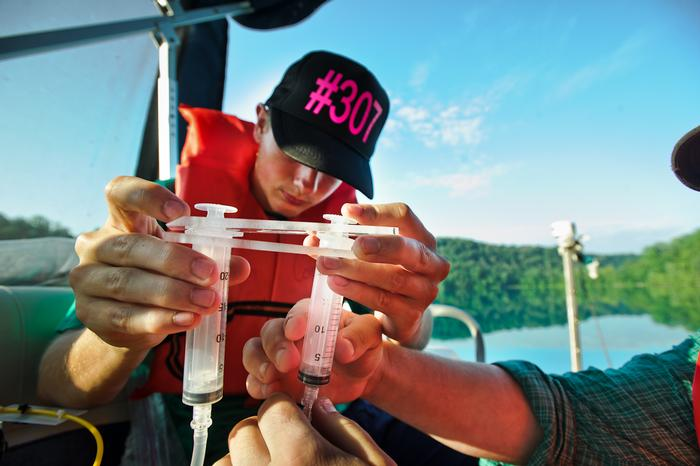 Rob Clayton '15 assembles the series of syringes that will collect bacteria samples in the lake. PHOTO: BY NANCY L. FORD