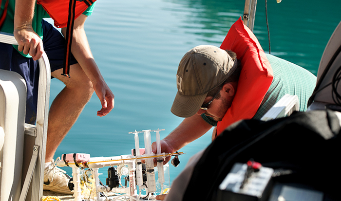 Rob Clayton, left, and Daniel Lichtenauer, remove a sample syringe containing bacteria samples from Green Lake. PHOTO: BY NANCY L. FORD