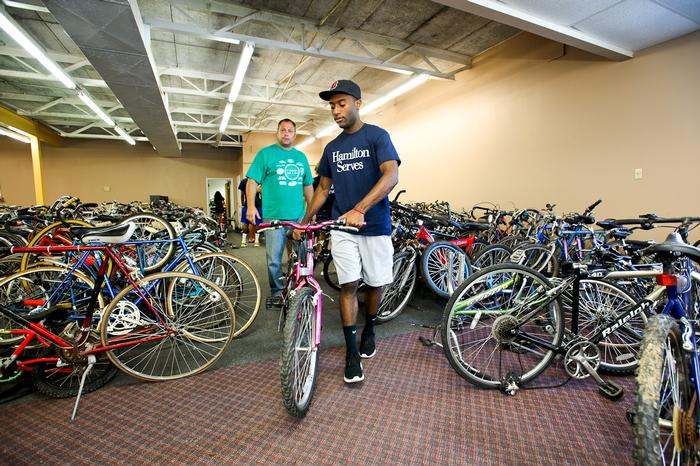 Branden Miles '17 helps organize bikes at the Underground Cafe Bike Shop. PHOTO: BY NANCY L. FORD