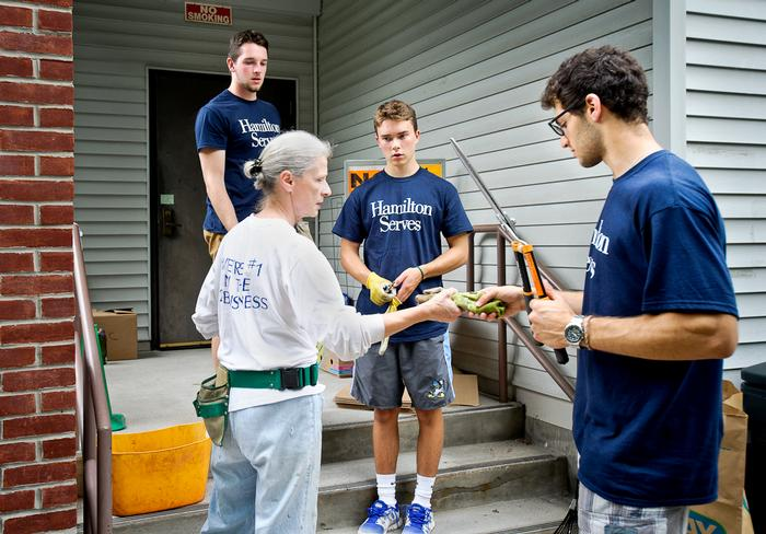 Dan Horgan '18 (left), Michael Mac Bolder' Houghton '18, and Jared Mandelbaum '18 accept supplies from Kris Bellona as they volunteer at Kirkland Town Library. PHOTO: REBECCA SHEETS