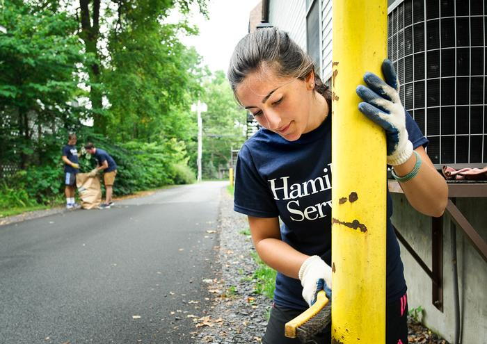Hanna Meisels '18, scrapes paint off of caution poles while volunteering at Kirkland Town Library. PHOTO: REBECCA SHEETS