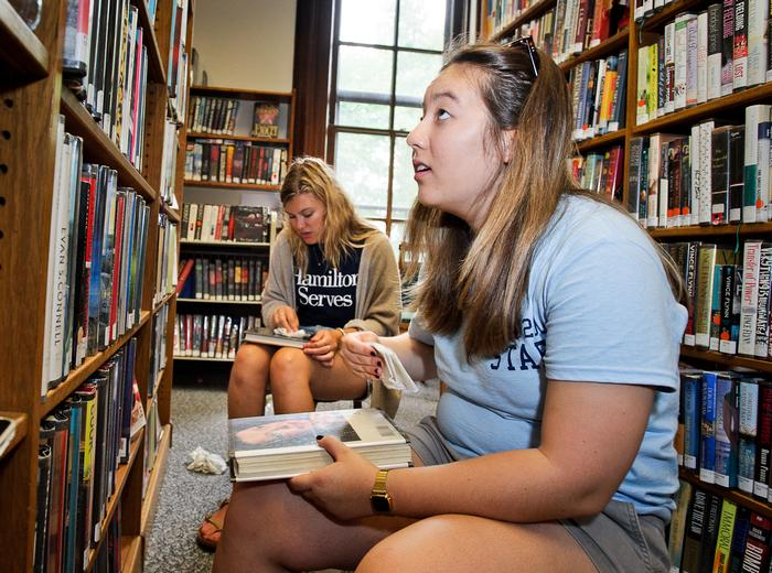 Julia Summers '18 and  Emichelle Woodward '17 wipe off books at the library. PHOTO: REBECCA SHEETS