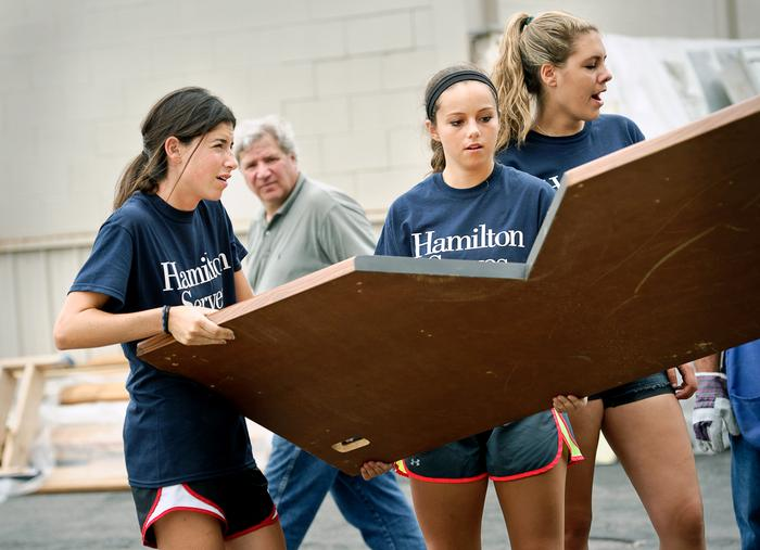 Hanna Jerome '18 helps lift wood while volunteering at the Habitat for Humanity store. PHOTO: REBECCA SHEETS