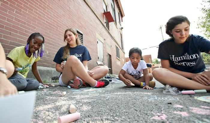 Hamilton College students Lina Garnett '17, left, and Samantha Rosen '17 help children chalk the sidewalk. PHOTO: BY NANCY L. FORD