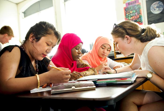 From left Sak Maya Rai, Asha Ahmed, and Cho Cho Win get a reading lesson from Hamilton alumna Sidika Kajtezovic '14, PHOTO: NANCY L. FORD